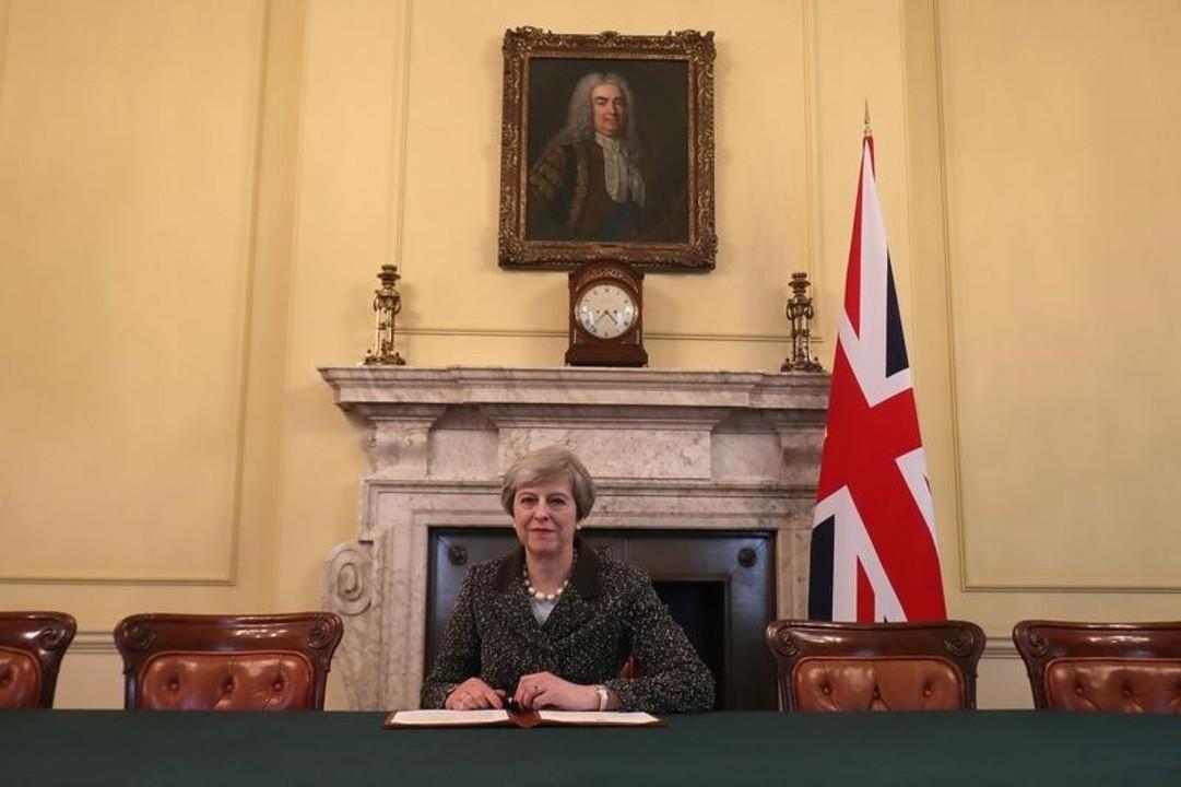 署名するメイ首相