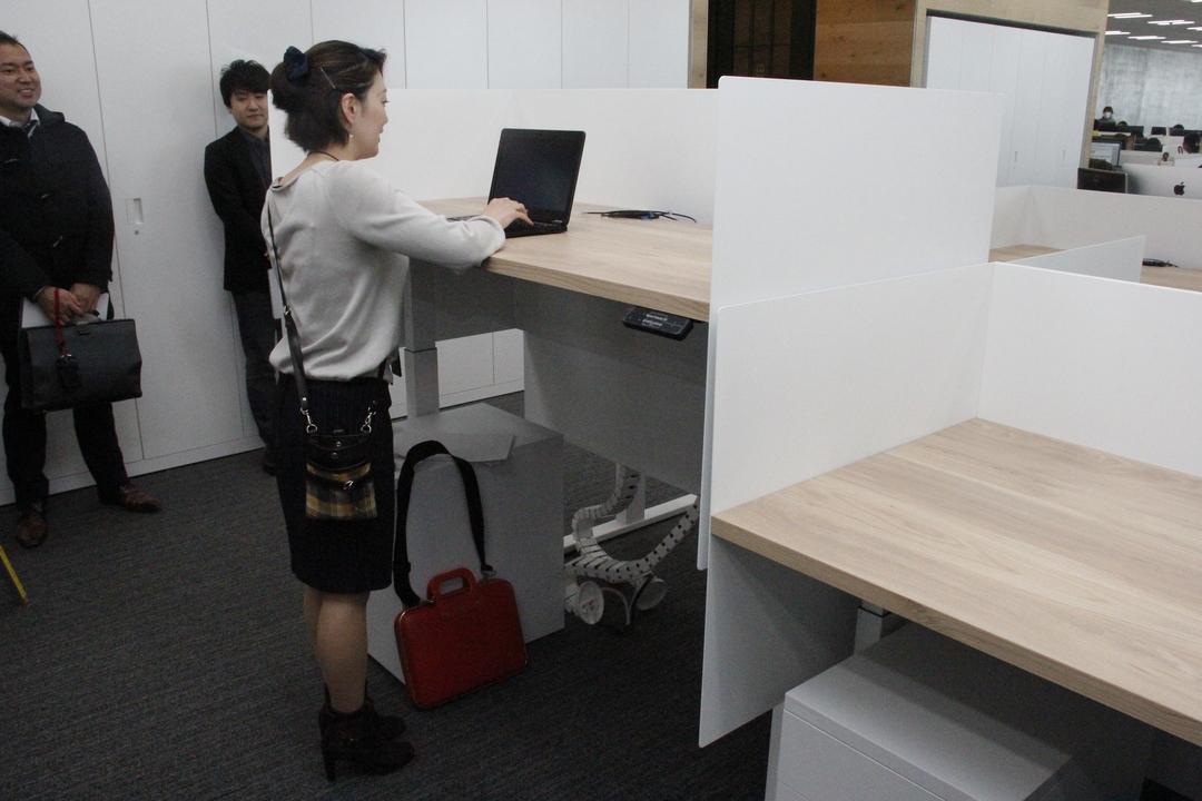 高さが調節できるデスクの前に立つ女性。