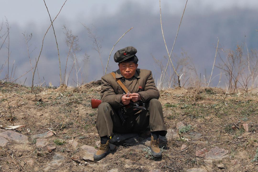 鴨緑江の土手に座る北朝鮮の兵士。
