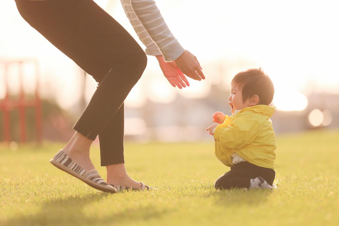 小さな男の子を抱き上げようとする母親