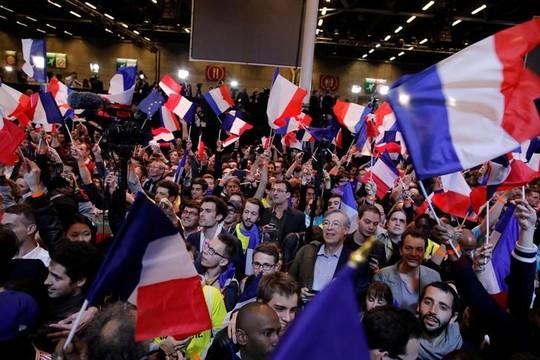 フランス国旗を掲げて選挙結果に注目する人々