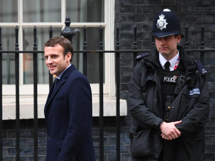 微笑みながら歩くエマニュエル・マクロン氏とその隣に立つ警察官。