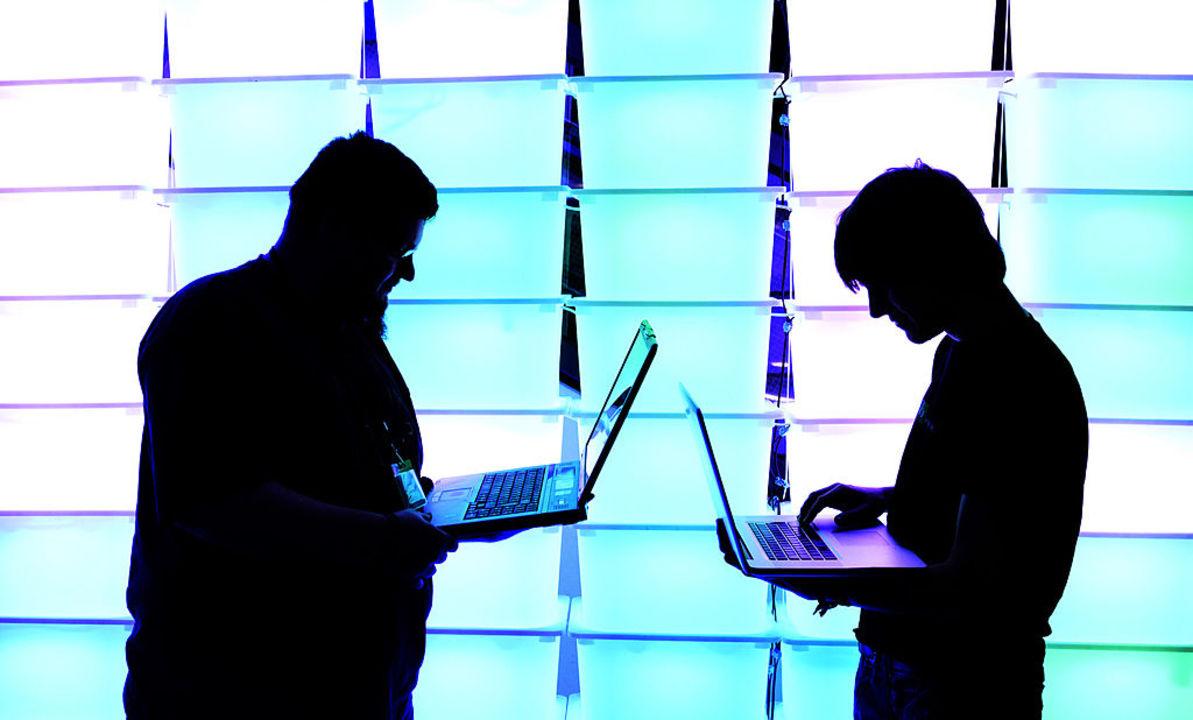 手にラップトップを持った男性二人が向かい合っている写真。