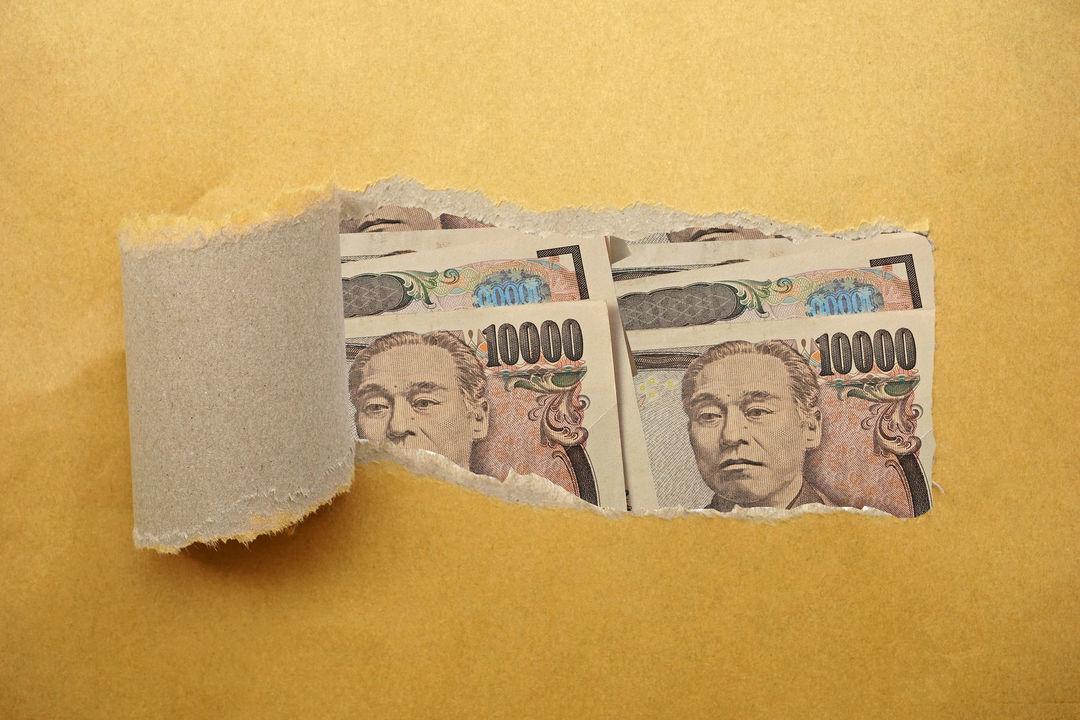 破れた紙の向こう側に覗く複数の一万円札