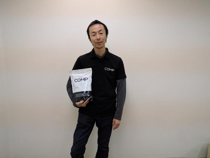 COMPのCEO・鈴木優太氏が製品を手に持ち立っている。