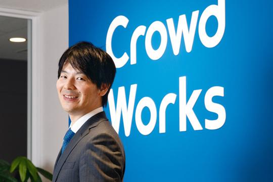 クラウドワークス社のロゴの前で微笑む吉田浩一郎社長