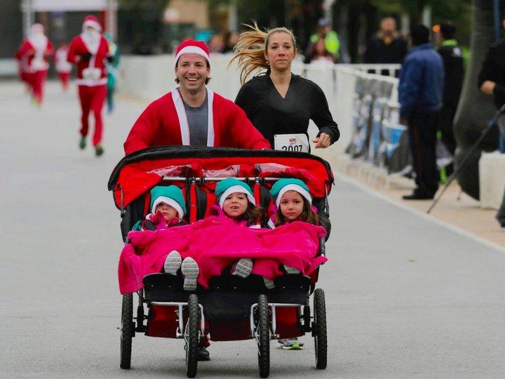 サンタクロースの服を着て3つ子のベビーカーを押す男性