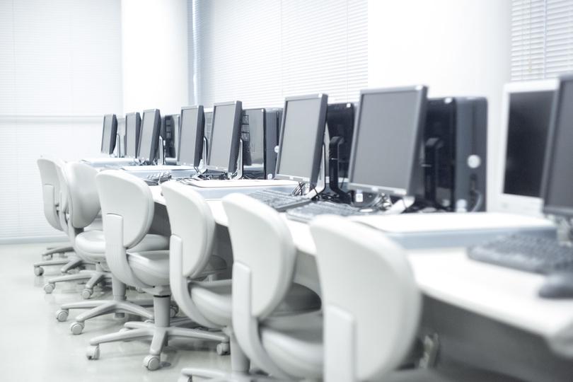 誰もいないオフィスに並ぶデスクトップパソコン
