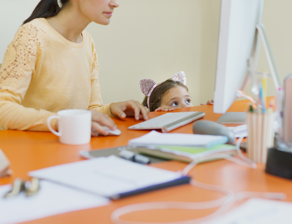 パソコンに向かう母親と隣で遊ぶ子ども