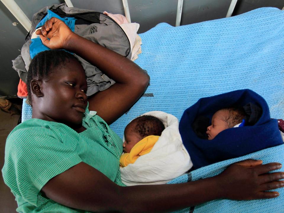 ベッドで眠っている乳児を見守る黒人女性