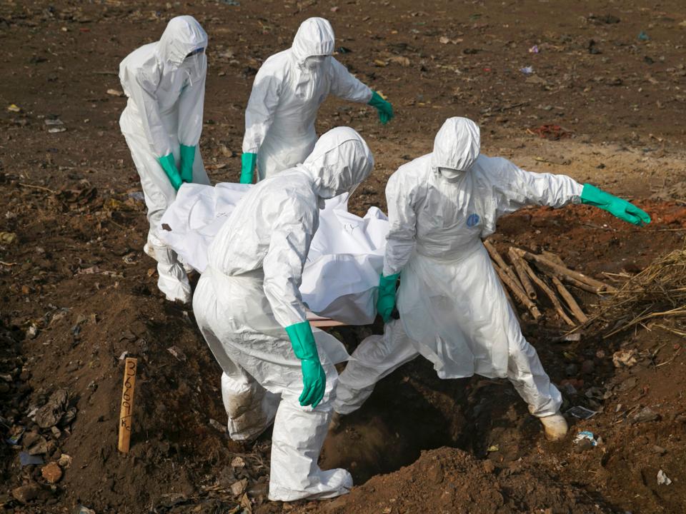 防護服を着用した人々が伝染病で亡くなった人を埋葬している