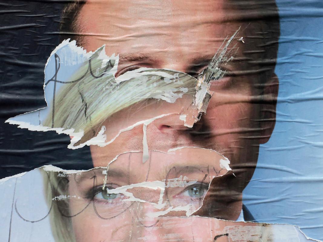 ルペン候補の選挙ポスターの上から貼られたマクロン候補のポスターの写真