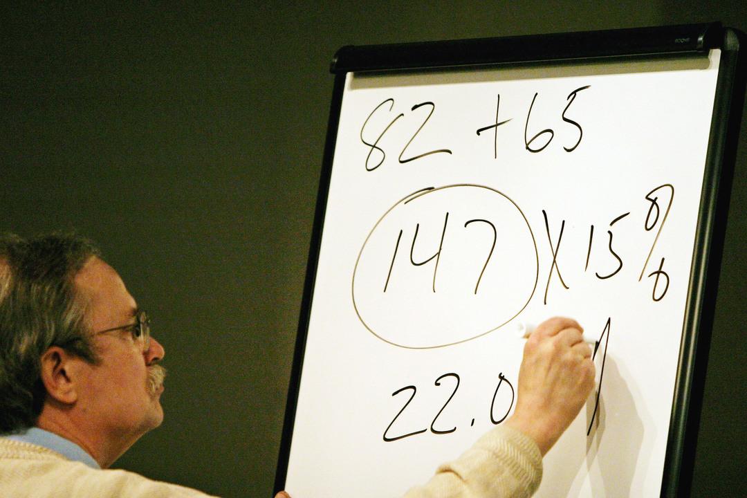 ホワイトボードに数式を記す初老男性