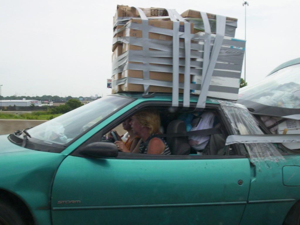 補修テープでぐるぐる巻きにした荷物を運ぶ自動車