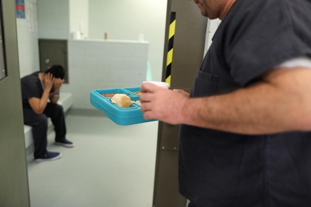 移民収容施設内で、食事を運ぶ拘留者