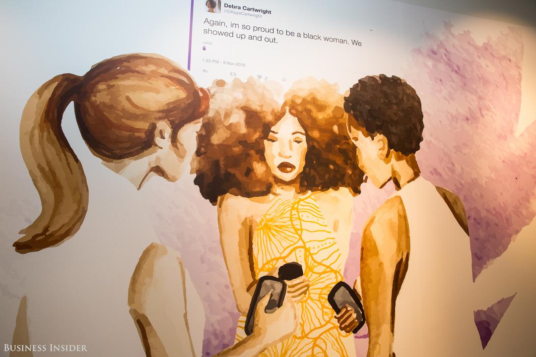 3人の女性がスマートフォンを手に持って輪になっている様子が描かれた壁画