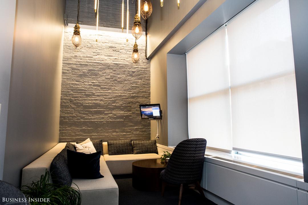 L字型のソファ、イスと小さなテーブル、スクリーンがある部屋