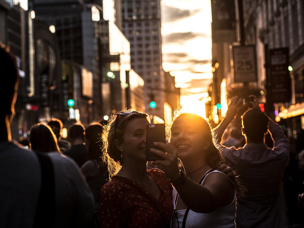 マンハッタンヘンジを背景にセルフィーを撮影する人々