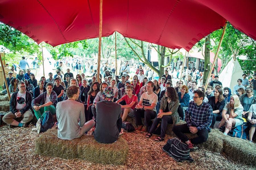 赤い傘の下で講演を聞く人々