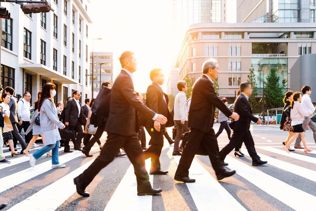 光の刺す横断歩道を歩くビジネスパーソン