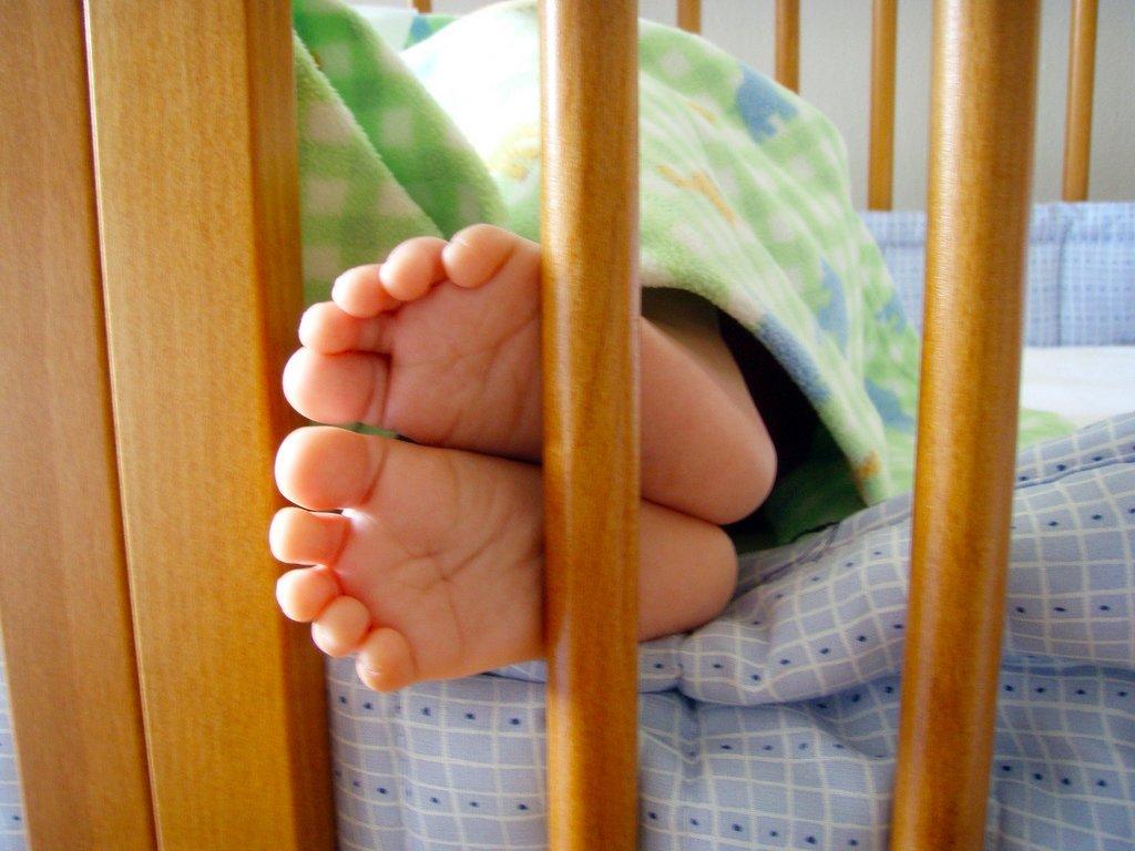 子ども用ベッドで寝る子どもの足