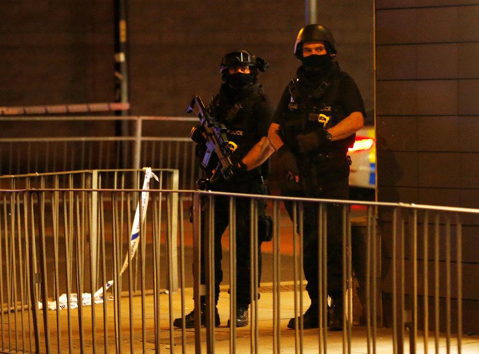 現場周辺に設置された通行止めの柵のなかに立つ武装警察官
