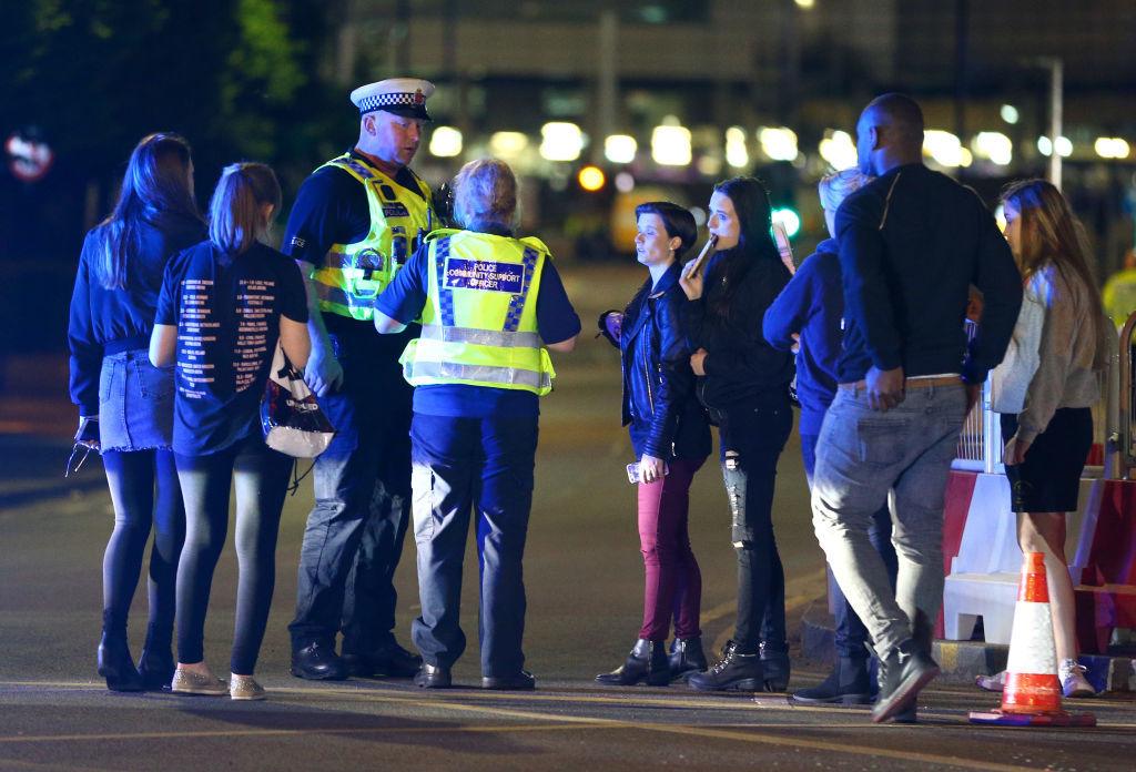 コンサート会場で事件に遭遇したファンに対応している警官