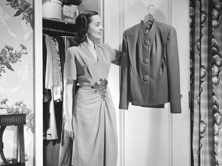 クローゼットからジャケットを取り出す女性(モノクロ)
