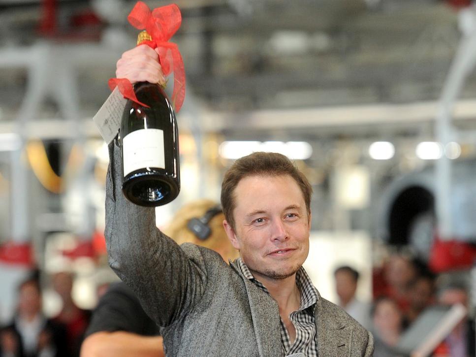 お祝いのシャンパンボトルを掲げるイーロン・マスク氏