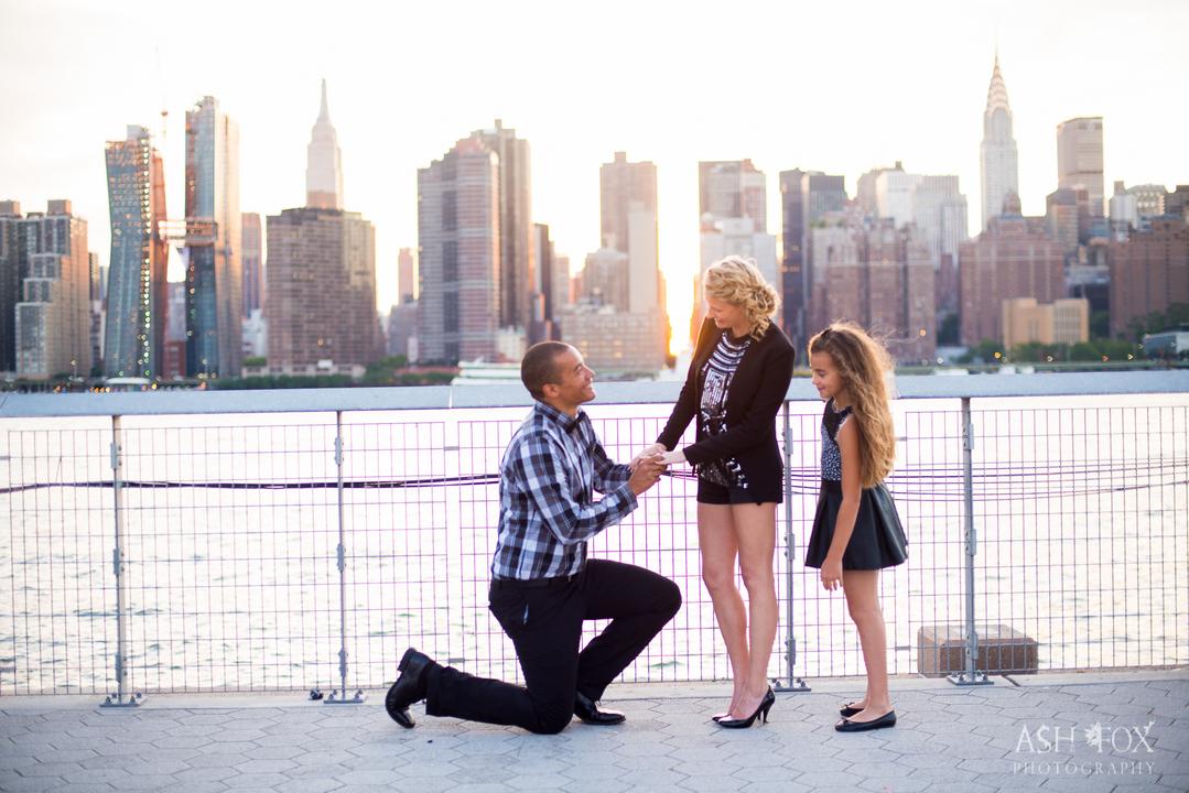 娘を連れた女性にひざまずきプロポーズする男性。
