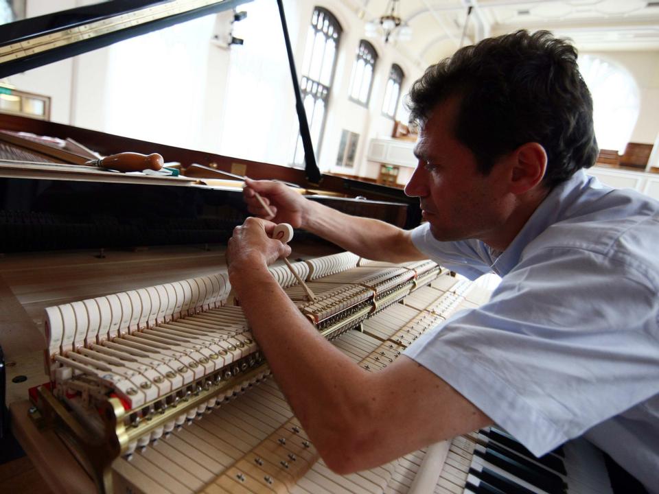 グランドピアノを調律している人の様子