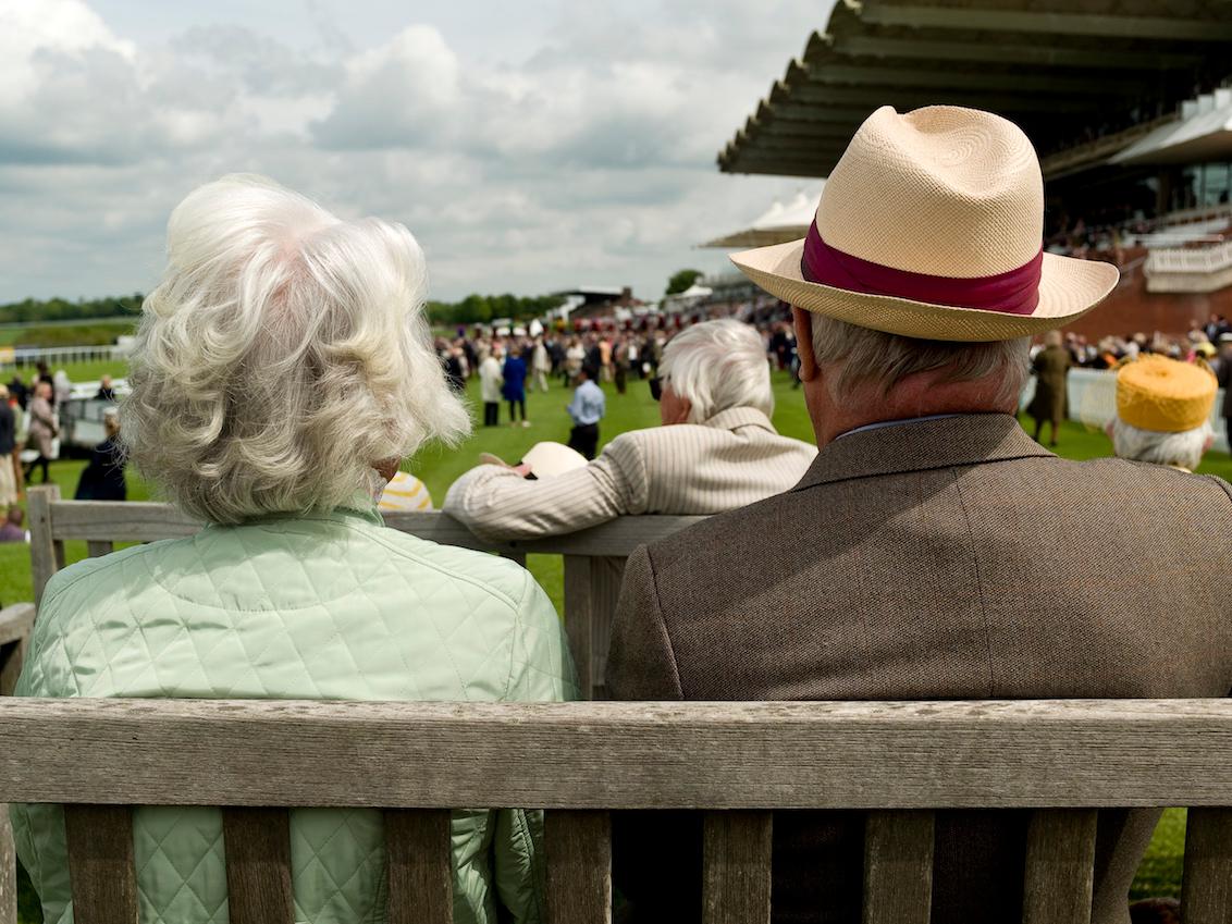老いた男女が肩を並べてベンチに座っている様子