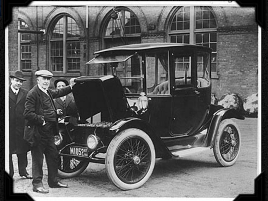 電気自動車のボンネットに手をかけるトーマス・エジソン