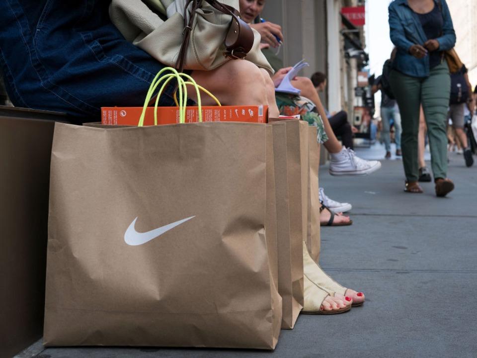 ナイキのロゴが入った買い物袋を持つ人