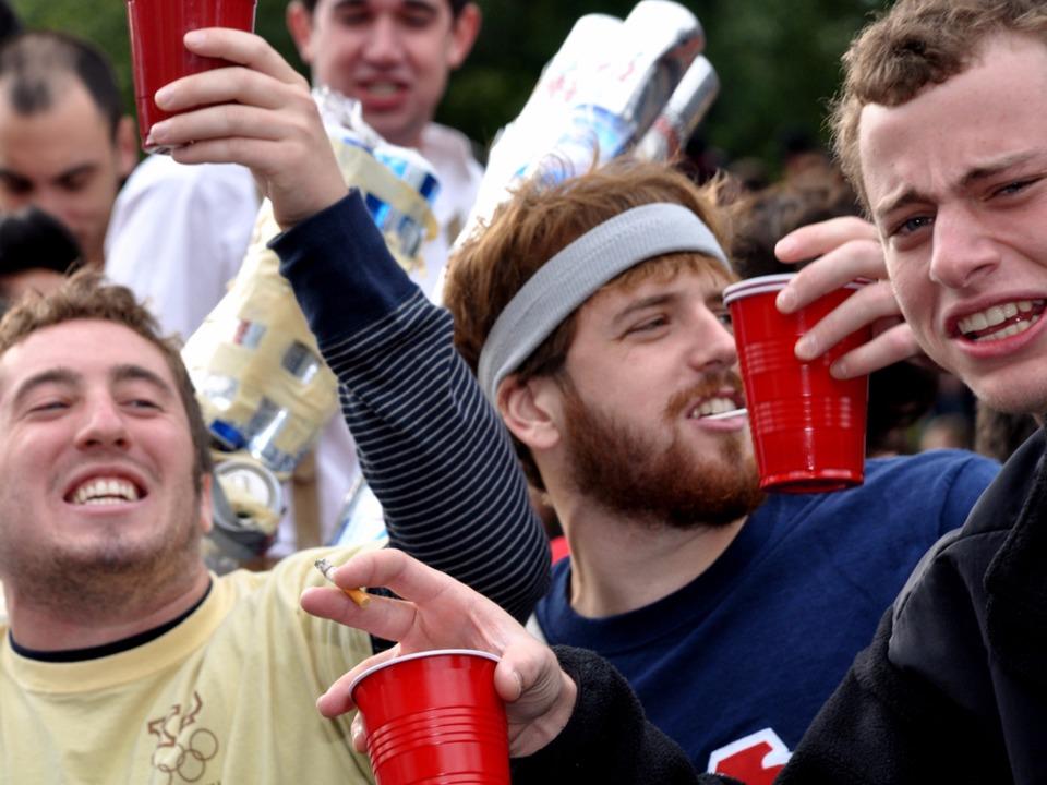 ドリンクのカップを片手に盛り上がる若い男性たち