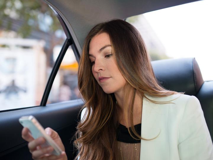 車の中でスマホを使う女性