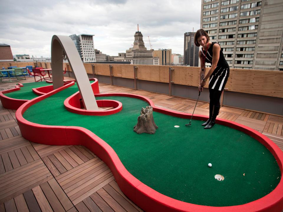 屋上でミニチュアゴルフを楽しむ人