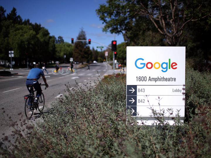 グーグルの看板と脇を自転車で走る男性