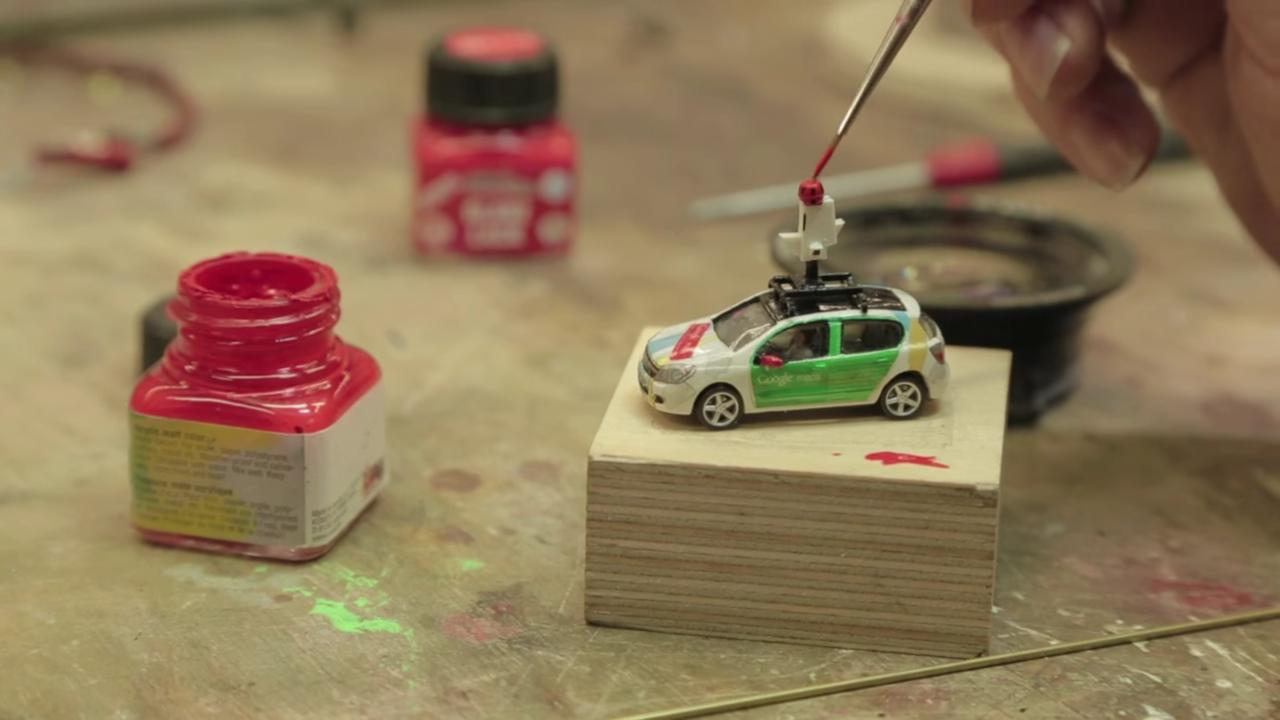 ミニチュアカー上部に取り付けた超小型カメラを筆で彩色している様子