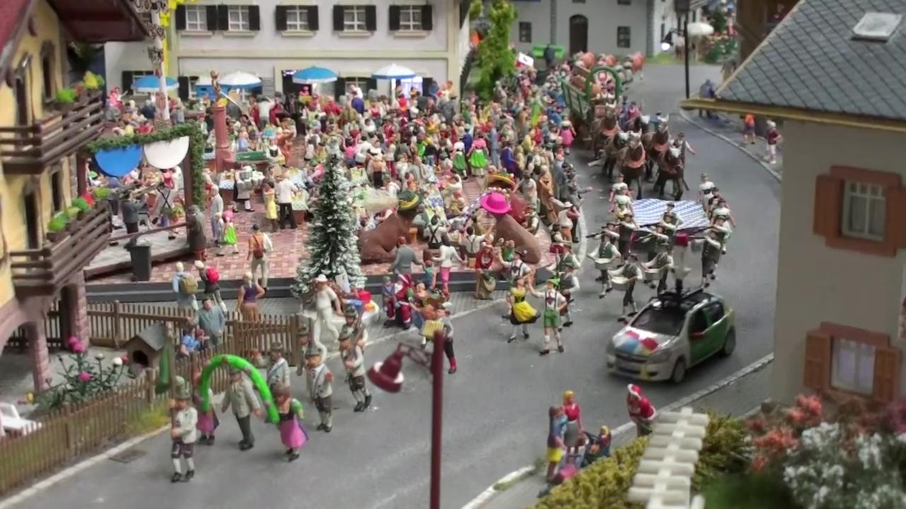 オクトーバーフェストの様子。広場では人々がビールを飲み、路上をパレードが通り過ぎていく