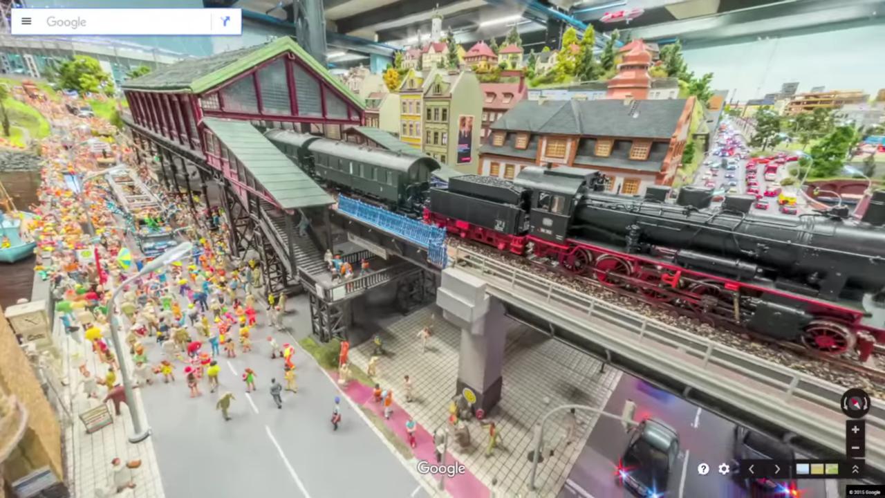 ハンブルクの駅舎へ入っていく電車と、その下の通りを過ぎていくパレード