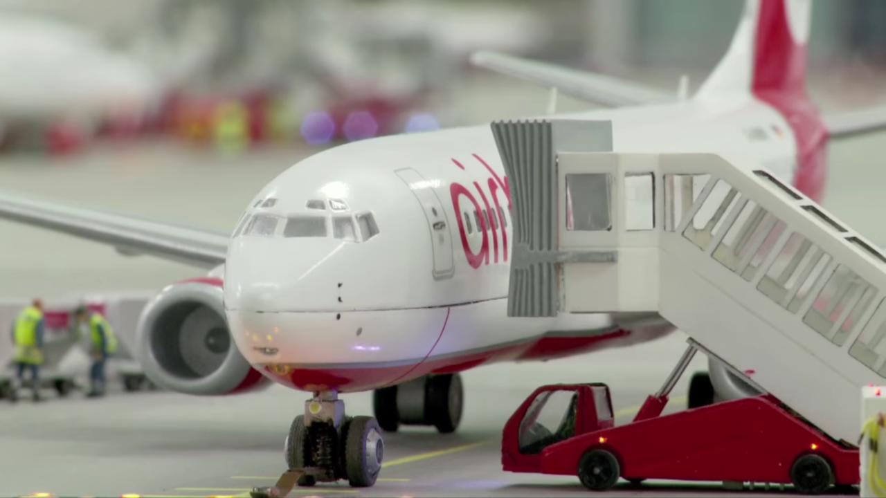 搭乗中の飛行機。移動式タラップが搭乗口に取り付けられ、遠くには空港作業員の姿も