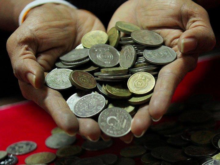 スリランカのコインを見せる男性