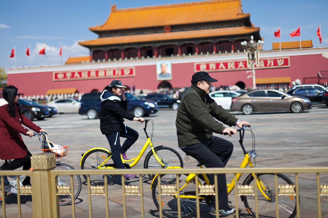 天安門の前を自転車で通る人たち
