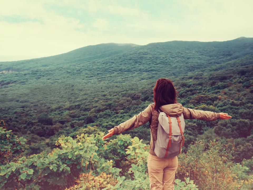 山登り中に深呼吸する女性