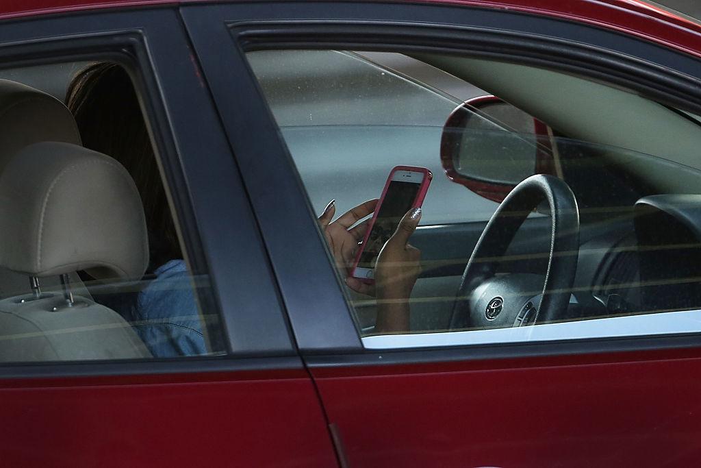 車内でスマホを操作する女性の写真
