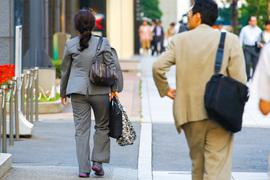 働く女性と男性の後ろ姿
