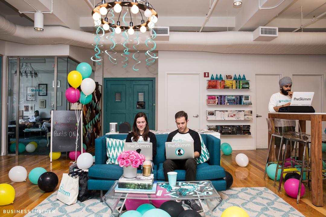 theSkimmのオフィス内部。明るい青緑のカーリングリボンがシーリングランプを飾り、カラフルなバルーンがフロアに散らばっている