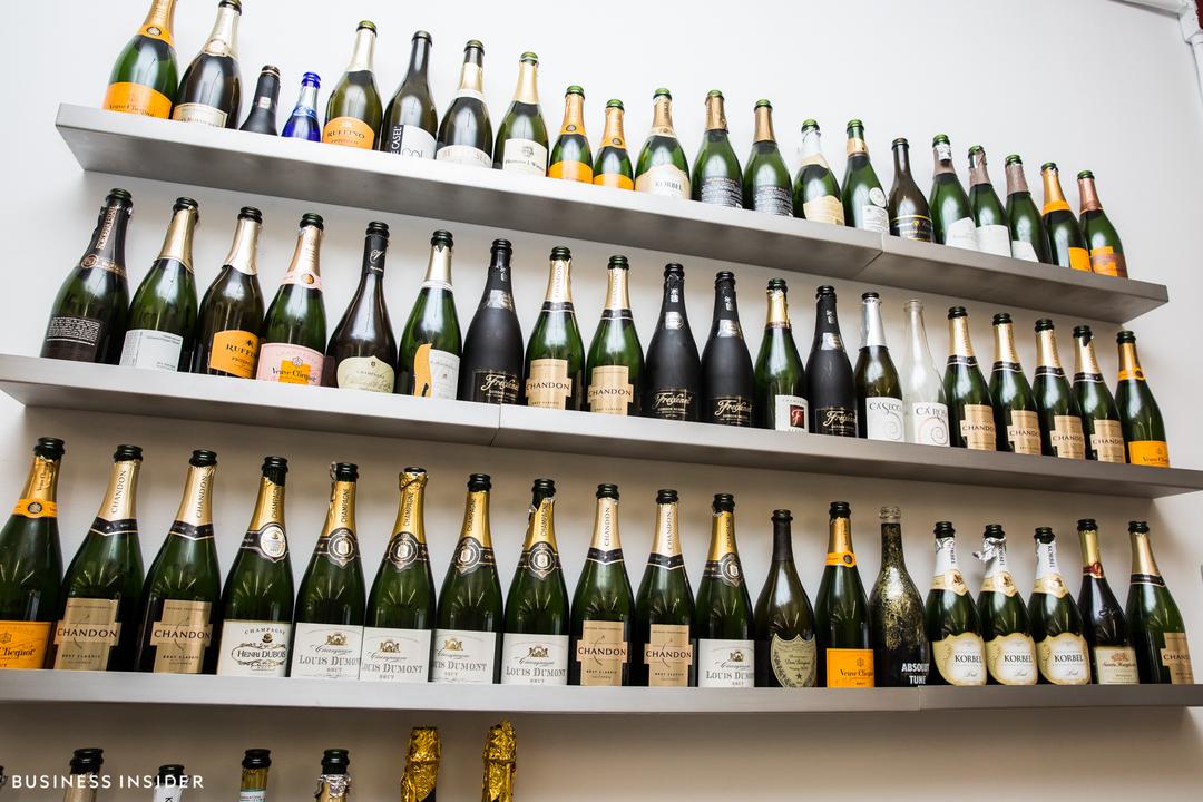 壁の棚にずらりと並ぶシャンパンボトル