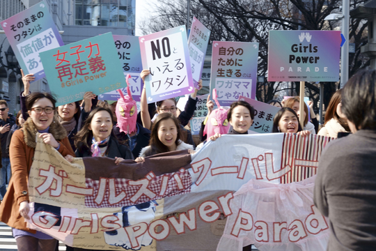 「ガールズ・パワー・パレード2016」と書かれた横断幕を持って歩く人々